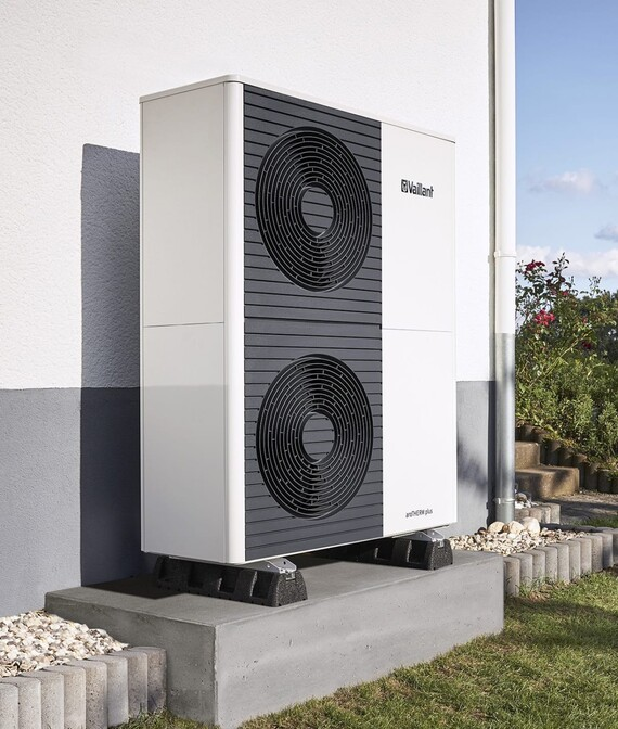 heat pump aroTHERM plus in the garden infront of a housewall of a new building.